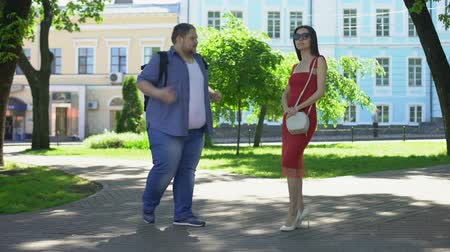 perdente : Young overweight man talking to slim lady in park, pretty girl ignoring fat guy Filmati Stock
