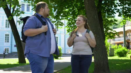 learning to walk : Fat university students talking and smiling, romantic date in park, friendship