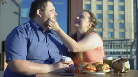 roliço : Smiling woman treating boyfriend french fries, fat couple date, unhealthy food