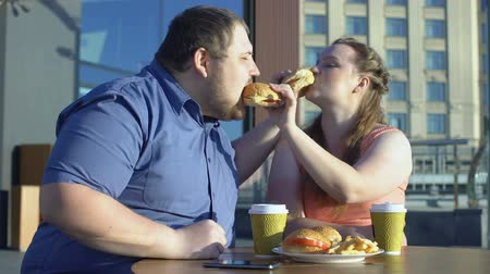 sedentary : Oversize couple sharing burgers during romantic date outdoors, calories and diet Stock Footage