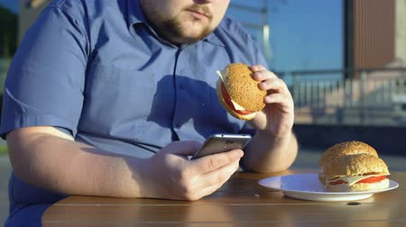sedentary : Lazy young man eating unhealthy burger and scrolling smartphone application Stock Footage