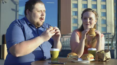 sedentary : Plump man and woman eating burgers and fries, colleagues having lunch outside Stock Footage