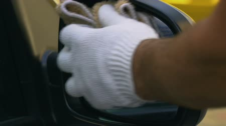 detailing : Car wash worker wiping side view mirror, using soap spray, automobile service