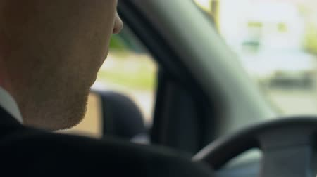go away : Private detective sitting in car, drinking coffee and eating doughnut. Stock Footage