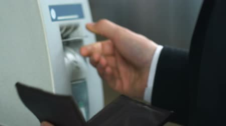bankomat : Man inserting credit card in ATM, problem with automated teller machine reader