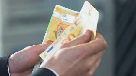rentável : Male hands recounting his salary, holding euro bills, budget cut and economics
