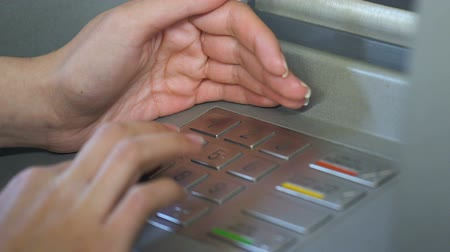 bankomat : Female entering her pin code and hiding keyboard of automated teller machine Wideo