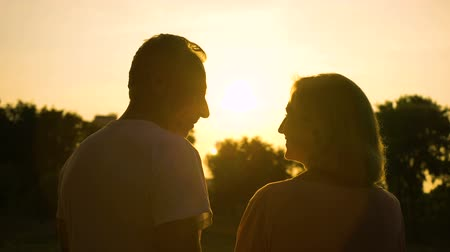 meghittség : Senior couple silhouette embracing, watching sunset together, romantic date