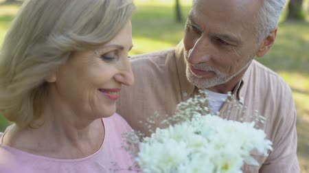 amado : Senior man giving flowers to beloved woman, pleasant surprise. Stock Footage