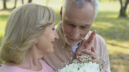 camomila : Senior couple on first date, man gives flowers to woman, mature love, romance