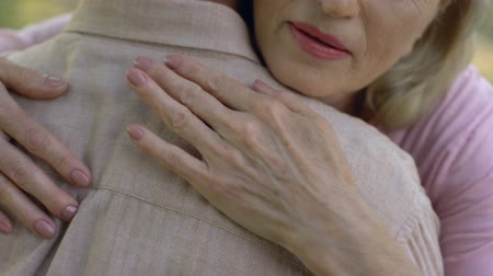 luto : Senior woman condolencing to man about disease or loss, support, care, closeup Stock Footage