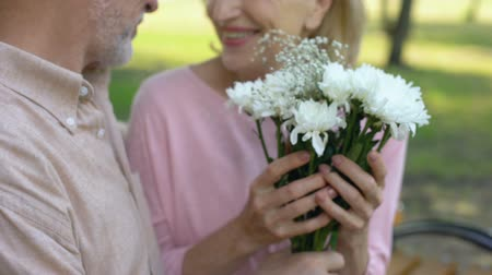 stokrotki : Old man giving bouquet of flowers to lady, floristics gifts, pleasant surprise Wideo