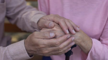 guy home : Aged male covering female hands, nursing home care, family support, assistance