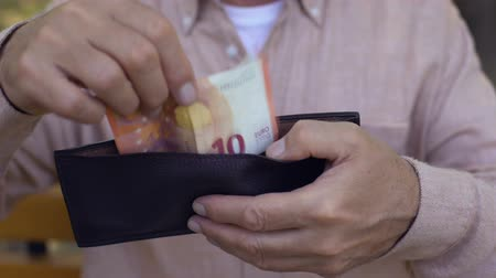 ganhos : Old male hand putting euro bill wallet, bank system, pensioner poverty, budget