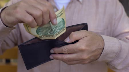 пенсионер : Poor pensioner putting dollar banknote in empty wallet, low retirement payment