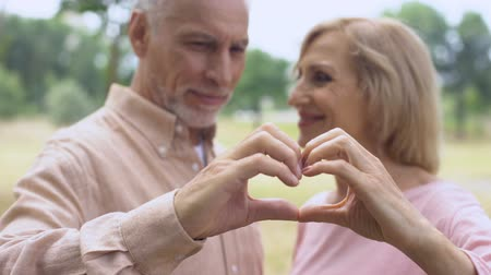 two hearts : Happy senior couple showing heart gesture, love togetherness, soul mates romance