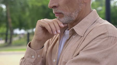 思考 : Serious aged man with hand on chin planning purchase, health problem, choice