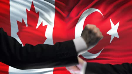 colision : Canada vs Turkey confrontation, countries disagreement, fists on flag background