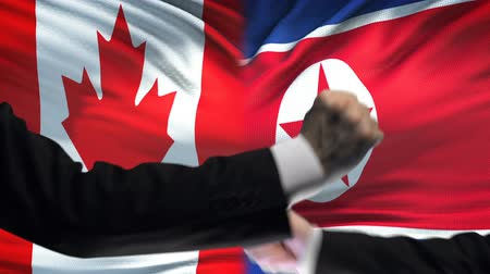 oposição : Canada vs North Korea confrontation, fists on flag background, diplomacy Vídeos