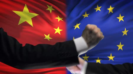 diffidenza : China vs EU confrontation, countries disagreement, fists on flag background