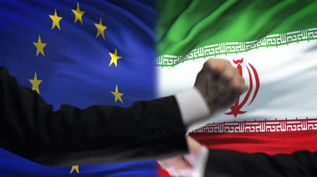кризис : EU vs Iran confrontation, countries disagreement, fists on flag background Стоковые видеозаписи