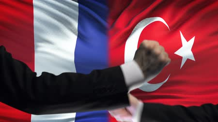 diffidenza : France vs Turkey confrontation, countries disagreement, fists on flag background