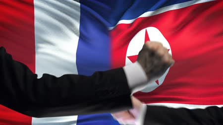 oposição : France vs North Korea confrontation countries conflict, fists on flag background