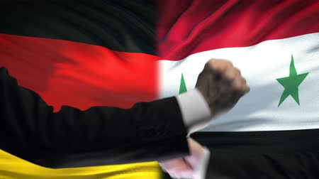 oposição : Germany vs Syria confrontation, countries disagreement, fists on flag background