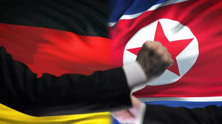 diffidenza : Germany vs North Korea confrontation, fists on flag background, diplomacy