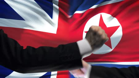 colision : Great Britain vs North Korea confrontation, fists on flag background, diplomacy