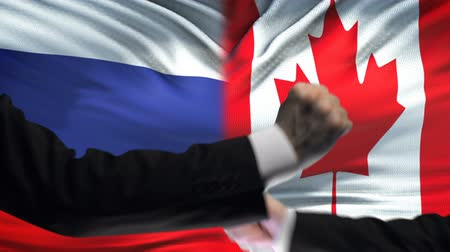 oposição : Russia vs Canada confrontation, countries disagreement, fists on flag background