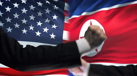 confronto : US vs North Korea confrontation countries disagreement, fists on flag background