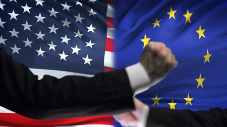 confronto : US vs EU confrontation, countries disagreement, fists on flag background