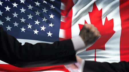 dispute : US vs Canada confrontation, countries disagreement, fists on flag background