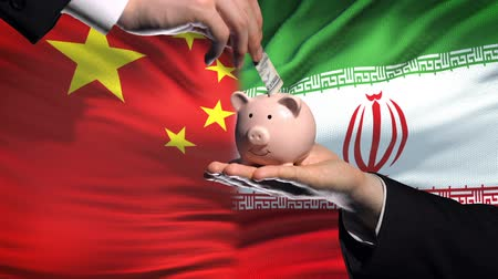 投資家 : China investment in Iran, hand putting money in piggybank on flag background