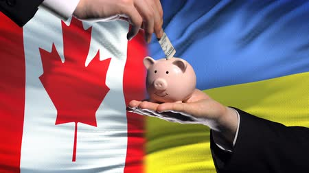 投資家 : Canada investment in Ukraine, hand putting money in piggybank on flag background