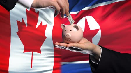 yeniden yapılanma : Canada investment in North Korea hand putting money in piggybank flag background