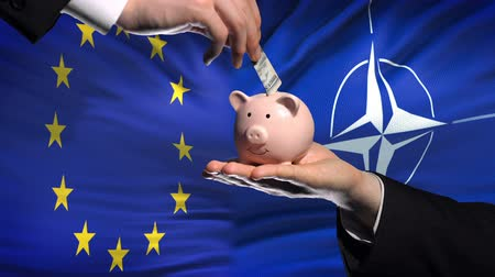 投資家 : BRUSSELS, BELGIUM - CIRCA JUNE 2018: EU investment in NATO, hand putting money in piggybank on flag background