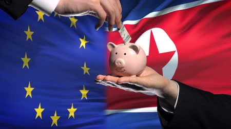 投資家 : EU investment in North Korea, hand putting money in piggybank on flag background