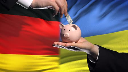 yeniden yapılanma : Germany investment in Ukraine hand putting money in piggybank on flag background