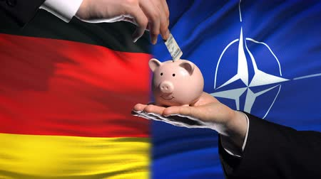 yeniden yapılanma : BRUSSELS, BELGIUM - CIRCA JUNE 2018: Germany investment in NATO, hand putting money in piggybank on flag background Stok Video