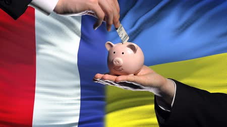 yeniden yapılanma : France investment in Ukraine, hand putting money in piggybank on flag background