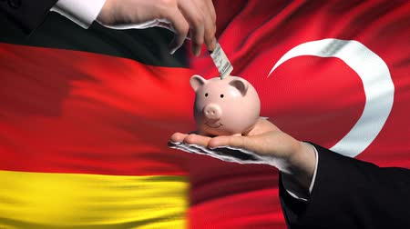 投資家 : Germany investment in Turkey, hand putting money in piggybank on flag background
