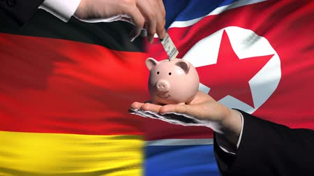 投資家 : Germany investment in North Korea, hand puts money in piggybank, flag background