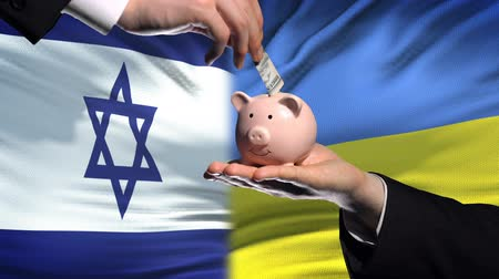 реализация : Israel investment in Ukraine, hand putting money in piggybank on flag background