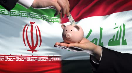 реализация : Iran investment in Iraq, hand putting money in piggybank on flag background