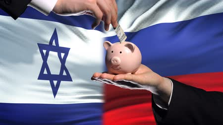 uygulanması : Israel investment in Russia, hand putting money in piggybank on flag background