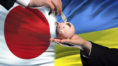 投資家 : Japan investment in Ukraine, hand putting money in piggybank on flag background