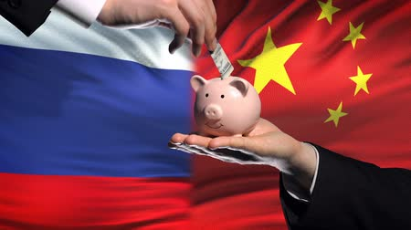 yeniden yapılanma : Russia investment in China, hand putting money in piggybank on flag background