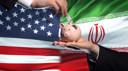 yeniden yapılanma : US investment in Iran, hand putting money in piggybank on flag background